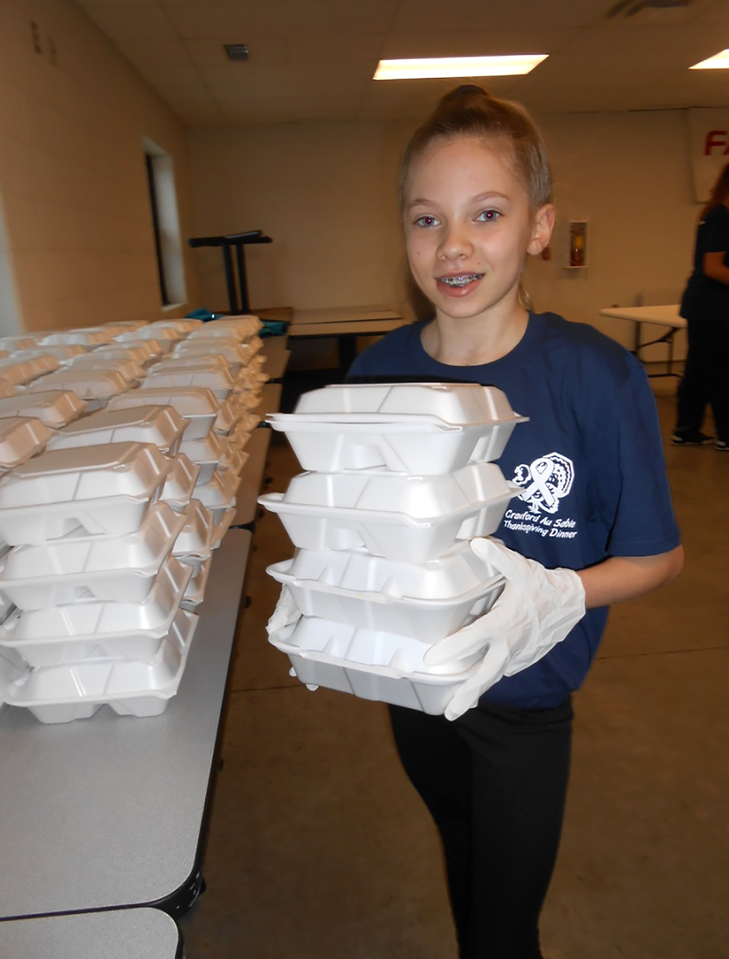 Luna Gauthier, age 11, carries a stack of containers to a table used to hold meals for packaging for deliveries.