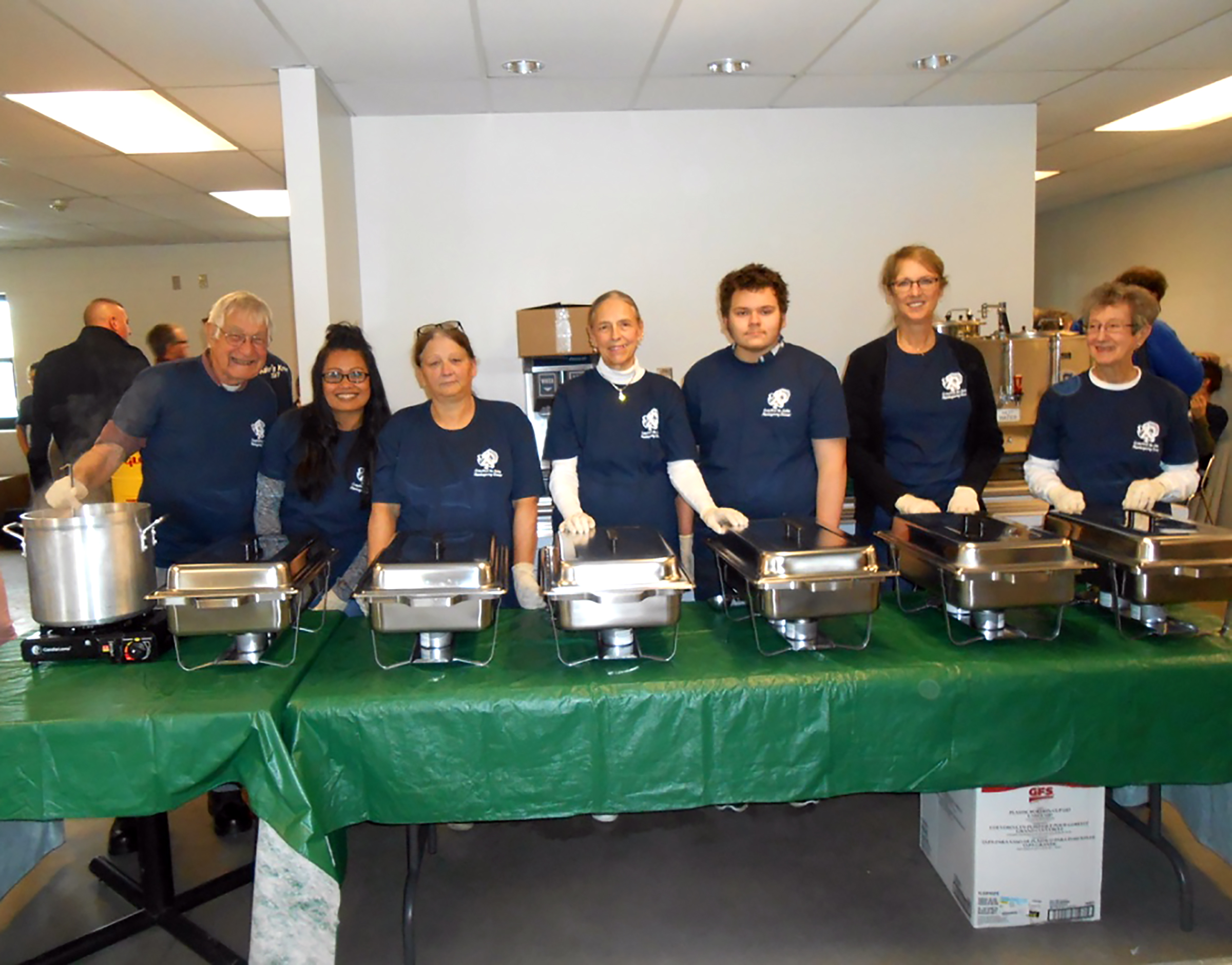Above, volunteers, who served up hot food items for home delivered meals, are pictured together at the Grayling Army Airfield dining hall.